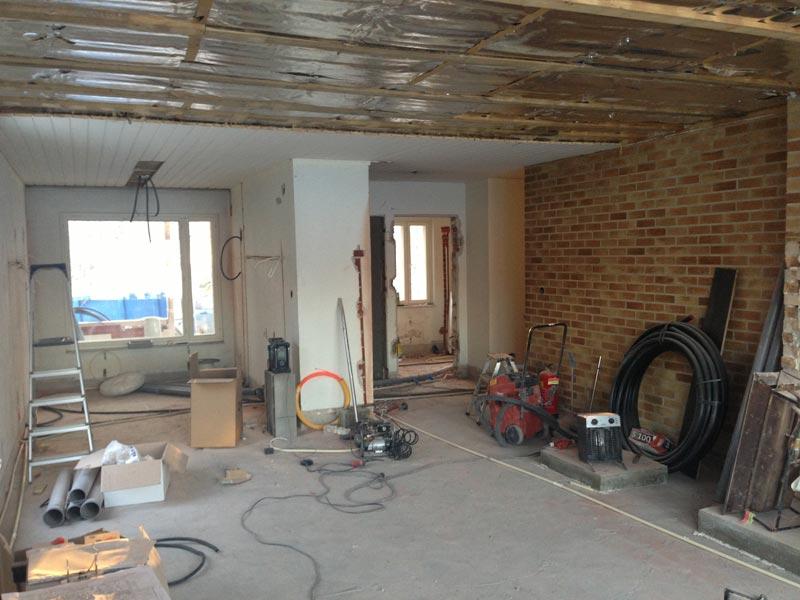 Näkymä olohuoneesta keittiöön ja eteiseen. Olohuoneen kattoa valmistellaan purettavaksi. Oikeaan reunaan takan viereen tulevat kierreportaat toiseen kerrokseen.