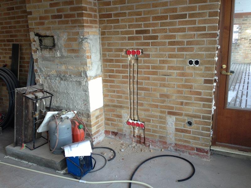 Olohuoneessa vedetään sähköjä. Takan paikalle on tehty betonipohja valmiiksi.
