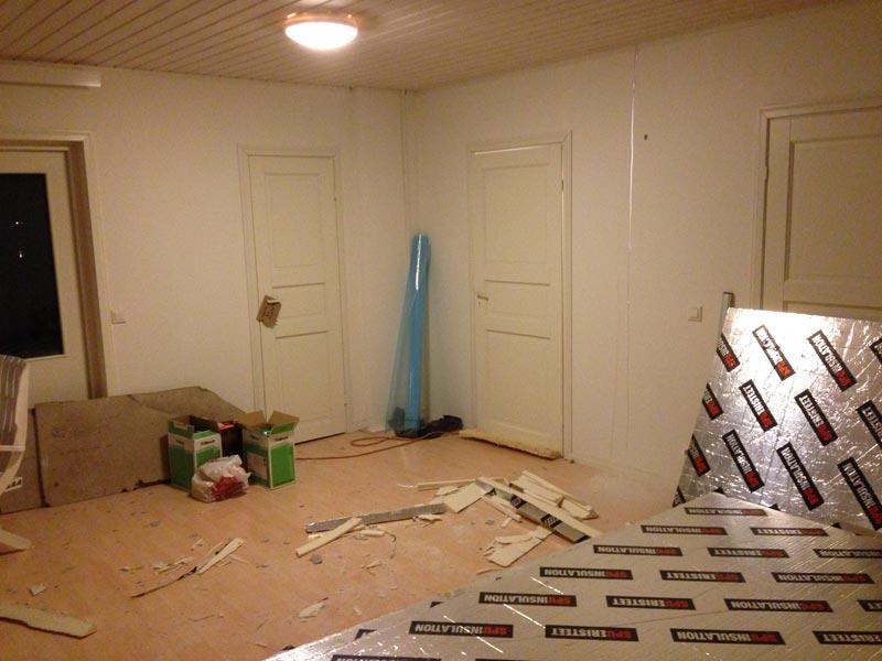 Poistuvan huoneen ovi vielä paikallaan. Seinä tosin leikattu jo auki, sillä valo kajastaa oven oikealta puolelta läpi.